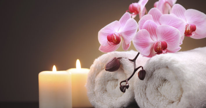 rolled towels, orchids and candles